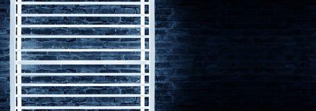 Construcción metálica rectangular iluminada por las lámparas de neón del LED Pared de ladrillo con la luz de neón imagenes de archivo