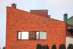 Construcción moderna de la cabaña del ladrillo rojo por una vida suburbana cómoda calefacción por la chimenea, humo de la chimene imagen de archivo