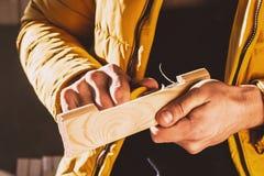 Construcción o trabajo de la reparación sobre la madera Primer de las manos del hombre que dan vuelta al bloque de madera con un  fotos de archivo