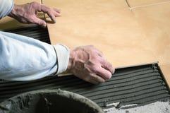 Construcción, poniendo las tejas en el piso imagen de archivo