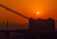 Construcción y sol poniente de puente Imágenes de archivo libres de regalías