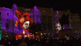 Construcci?n proyectando luces en la noche durante el festival ligero internacional de Bucarest del proyector almacen de metraje de vídeo