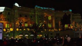 Construcci?n proyectando luces en la noche durante el festival ligero internacional de Bucarest del proyector metrajes