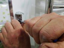 Construcci?n y reparaci?n - una herramienta y un destornillador profesionales en las manos del constructor foto de archivo libre de regalías
