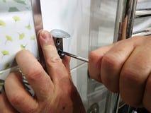 Construcci?n y reparaci?n - una herramienta y un destornillador profesionales en las manos del constructor imágenes de archivo libres de regalías