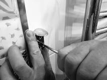 Construcci?n y reparaci?n - una herramienta y un destornillador profesionales en las manos del constructor fotografía de archivo libre de regalías