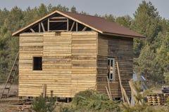 Construcción de la casa de madera en un bosque Imágenes de archivo libres de regalías