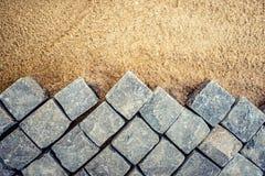 Construcción de los detalles del pavimento, pavimento del guijarro, bloques de la piedra en la construcción de carreteras Foto de archivo libre de regalías