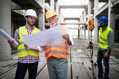 Η ομάδα των επιχειρηματιών στην ομάδα, ο αρχιτέκτονας και ο μηχανικός στο εργοτάξιο ελέγχουν τα έγγραφα στοκ φωτογραφίες