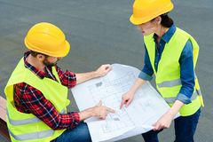 Construct colleagues in safety vests and helmets working with blueprint stock photography