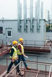Construct coworkers in safety vests and helmets with blueprint and tool belt. On roof stock photo