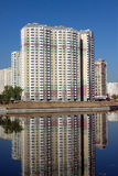 Constructed block of flats over river and clear blue sky in summer day Royalty Free Stock Photo