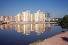 Constructed block of flats over river and clear blue sky in summer day Royalty Free Stock Photography