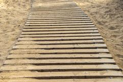 Constructed wooden walkpath in the sand at daytime royalty free stock image