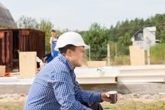 Constructeur assoiffé prenant une pause-café image stock