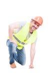 Constructeur attirant de sourire se mettant à genoux sur le plancher Photo libre de droits