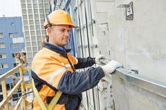 Constructeur aux travaux de construction de façade Photo stock