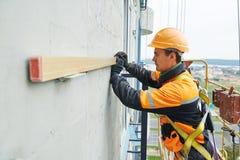 Constructeur aux travaux de construction de façade Photographie stock libre de droits