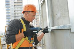 Constructeur aux travaux de construction de façade Photographie stock