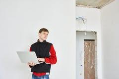 Constructeur avec l'ordinateur portable sur l'objet Photographie stock