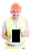 Constructeur beau montrant le comprimé moderne avec l'écran vide Photographie stock libre de droits