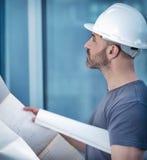 Constructeur d'architecte étudiant le plan de disposition de la salle Photos stock