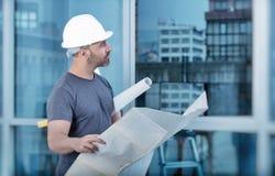 Constructeur d'architecte étudiant le plan de disposition des salles Photographie stock libre de droits