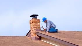 Constructeur d'entrepreneur avec le masque bleu réparant le toit photos libres de droits
