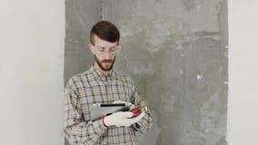 Constructeur dans la maison en construction utilisant le comprimé clips vidéos