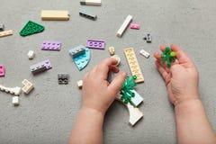 Constructeur dans les mains d'un enfant sur un fond gris avec un constructeur Habilet?s motrices fines photographie stock libre de droits