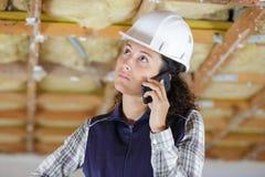 Constructeur de femme au téléphone photo libre de droits