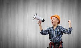 Constructeur de femme avec le mégaphone Photo stock