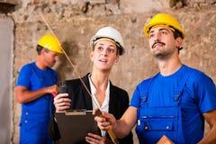 Constructeur et architecte discutant sur le chantier de construction photographie stock libre de droits