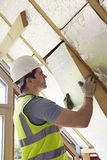 Constructeur Fitting Insulation Boards dans le toit de la nouvelle maison Photo stock
