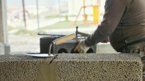 Constructeur fonctionnant avec des blocs de construction avec la truelle sur le premier plan photos libres de droits