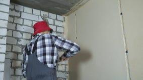 Constructeur masculin dans des lacunes remplissantes d'usage de travail dans le mur avec le plâtre avec l'espace libre clips vidéos