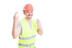 Constructeur masculin de sourire attirant faisant le double geste de chance Image libre de droits