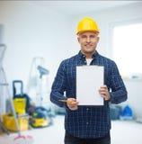 Constructeur masculin de sourire dans le casque avec le presse-papiers Photo libre de droits