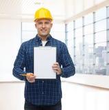 Constructeur masculin de sourire dans le casque avec le presse-papiers Photo stock
