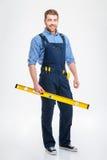 Constructeur masculin de sourire tenant des waterpas Images stock