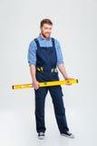 Constructeur masculin de sourire tenant des waterpas Photos libres de droits