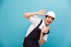 Constructeur masculin effrayé dans la bâche de casque de protection lui-même photos stock