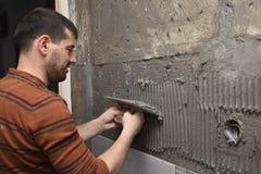 Constructeur professionnel appliquant la colle sur le mur image libre de droits
