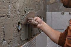 Constructeur professionnel appliquant la colle sur le mur photo libre de droits