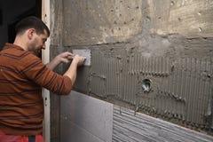 Constructeur professionnel appliquant la colle sur le mur photographie stock