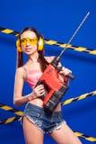 Constructeur sexy de brune sur un fond bleu avec un outil électrique dans les mains de Photo libre de droits