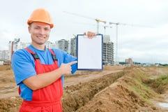 Constructeur souriant avec la planchette image stock