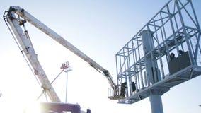 Constructeur sur une plate-forme d'ascenseur à un chantier de construction Hommes au travail échafaudage se réunissant de travail image stock