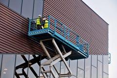 Constructeur sur une plate-forme d'ascenseur de ciseaux à un chantier de construction Photos stock