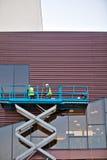 Constructeur sur une plate-forme d'ascenseur de ciseaux à un chantier de construction Images libres de droits